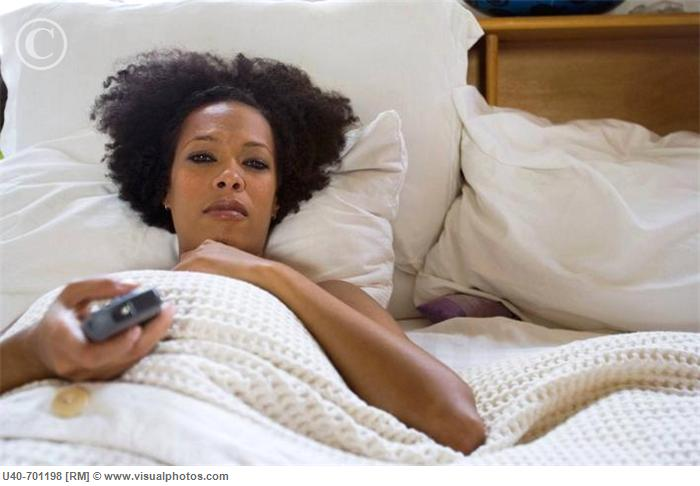 African American woman watching TV in bed