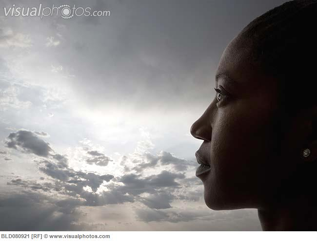 Profile of Black woman against cloudy sky